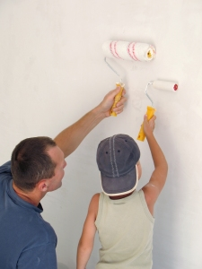 child and father painting wall together